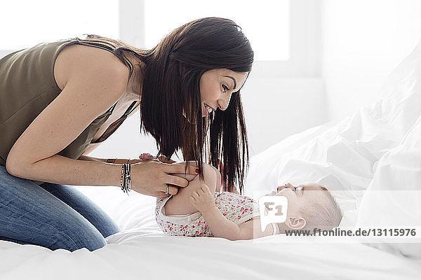 Seitenansicht der Mutter beim Spielen mit der zu Hause im Bett liegenden Tochter