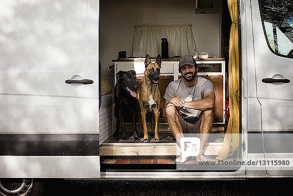 Porträt eines lächelnden Mannes  der mit Hunden im Wohnmobil sitzt