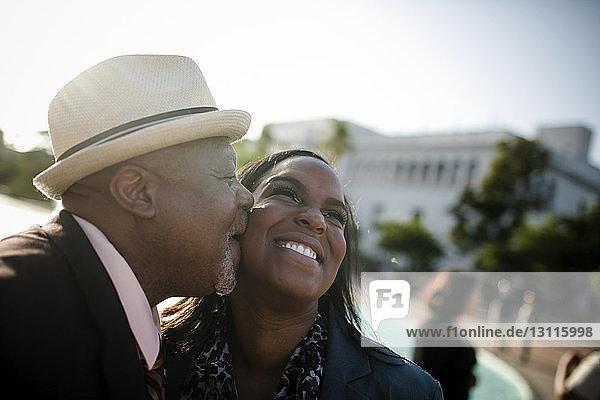 Nahaufnahme eines glücklichen Vaters  der seine Tochter küsst  während er gegen den klaren Himmel steht