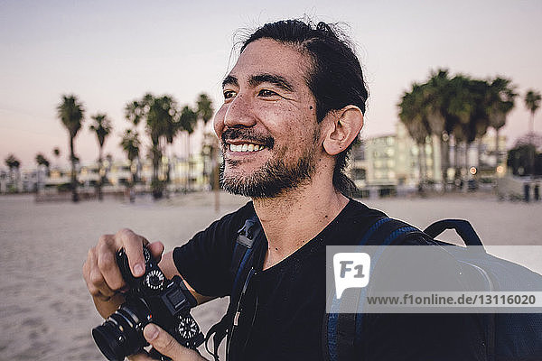 Close-up of smiling backpacker holding camera while looking away at beach