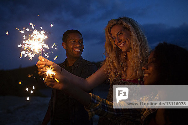 Friends holding illuminated sparklers at night