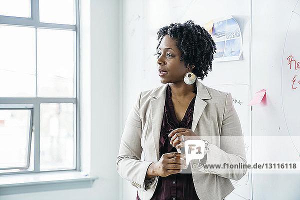 Geschäftsfrau spricht  während sie im Büro am Whiteboard steht