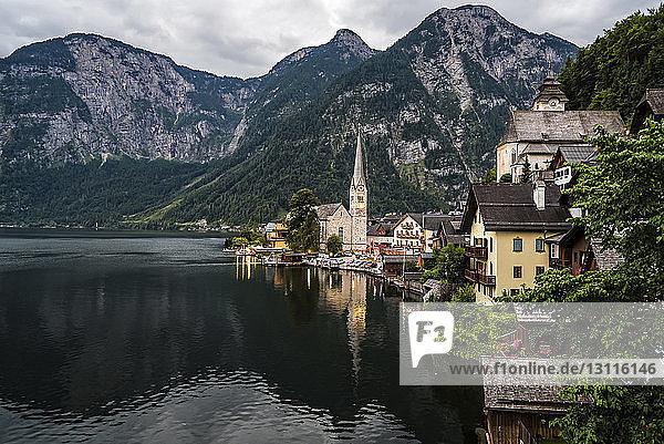Häuser und Kirche am See gegen Berge