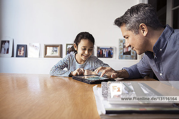 Father showing tablet computer to daughter