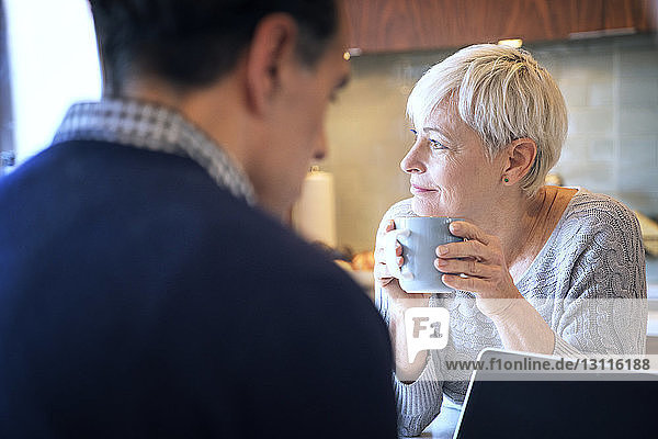 Thoughtful senior woman looking away while sitting by man at home