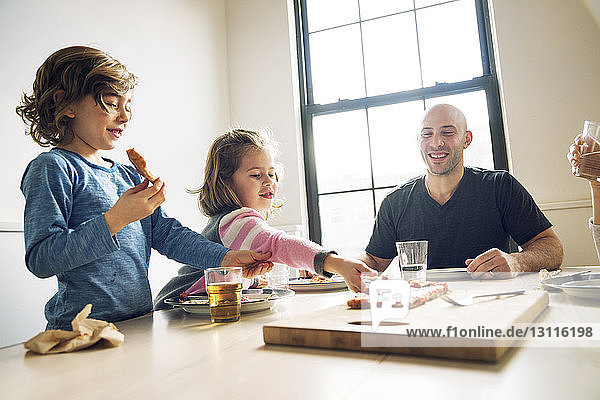 Girl picking pizza slice while sitting with family at dining table in home