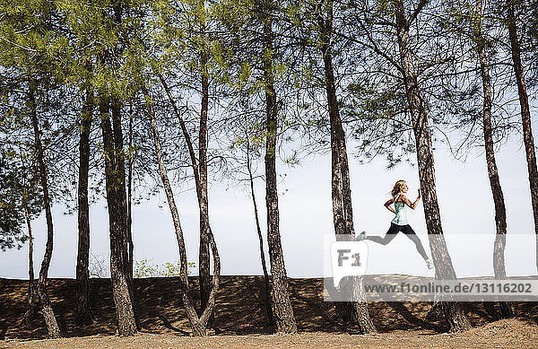 Frau joggt auf einem Feld inmitten von Bäumen