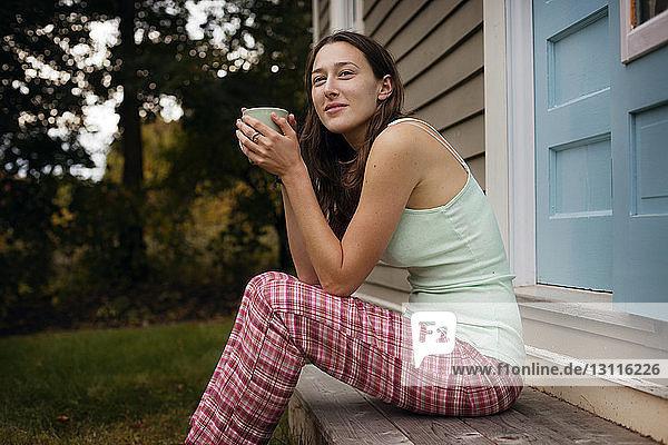 Nachdenkliche Frau lächelt  während sie eine Kaffeetasse vor dem Haus hält