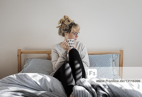 Woman holding coffee cup while sitting on bed at home