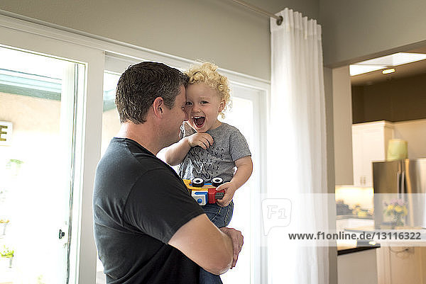 Portrait of cheerful son carried by father at home