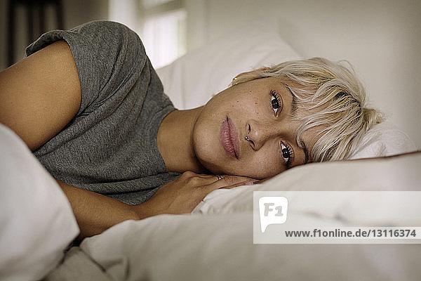 Porträt einer jungen Frau  die zu Hause auf dem Bett liegt