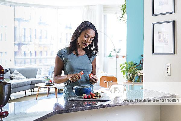 Frau schneidet Erdbeeren im Stehen zu Hause