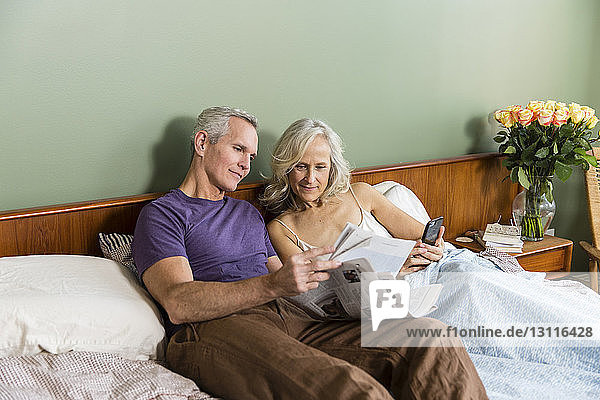 Couple reading newspaper while resting on bed at home