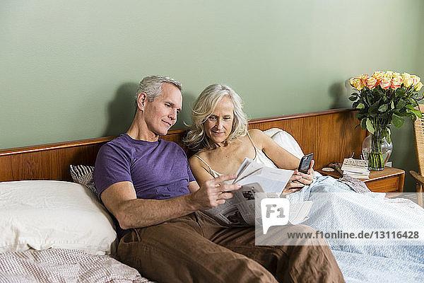 Paar liest Zeitung  während es zu Hause im Bett liegt