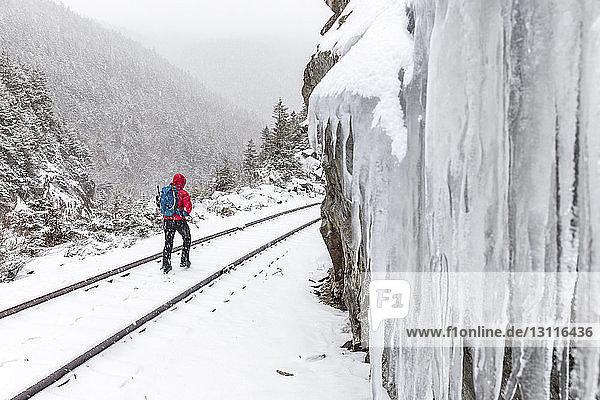 Rückansicht einer Frau  die während des Schneefalls in den White Mountains auf einer schneebedeckten Eisenbahnschiene geht