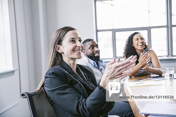 Glückliche Geschäftsleute applaudieren bei Sitzung im Sitzungssaal