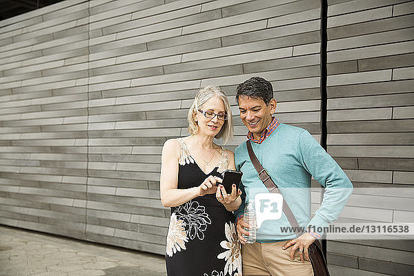 Mature couple using smart phone while standing against wall