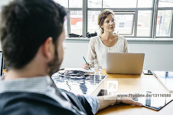 Geschäftsleute  die während einer Sitzung im Sitzungssaal sitzen