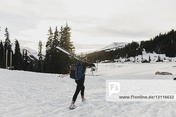 Young woman with backpack carrying ski on shoulder during winter