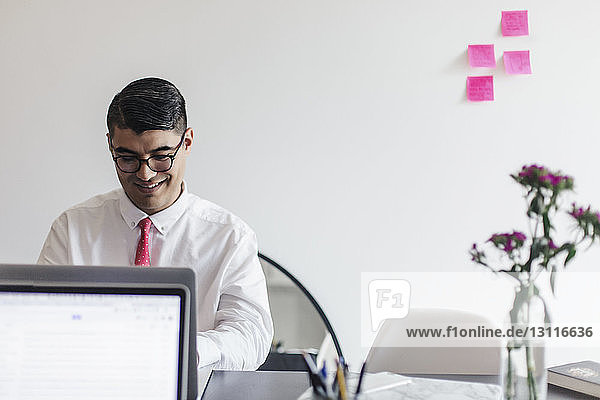 Smiling businessman using laptop computer at desk in office