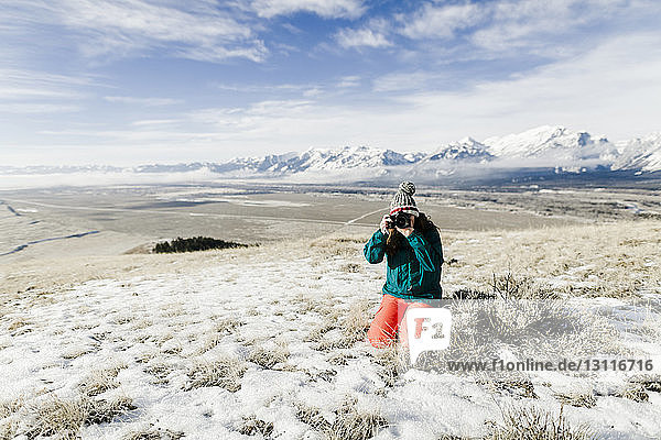 Female hiker photographing with camera while kneeling on snowy field against mountains
