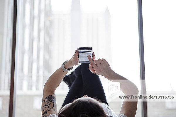 Frau benutzt Smartphone  während sie zu Hause am Fenster liegt
