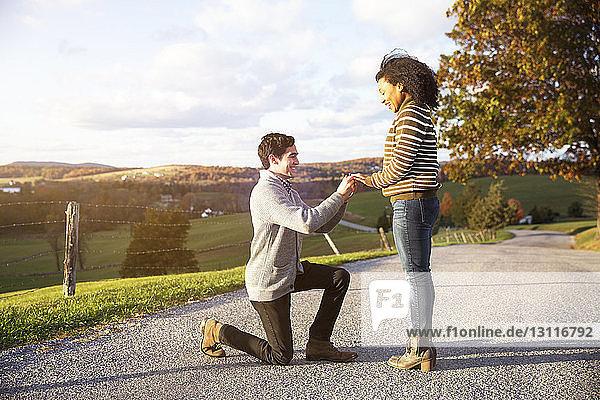Mann schlägt glückliche Freundin auf Fußweg vor