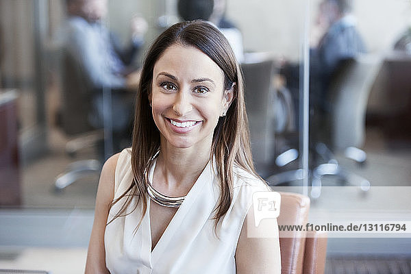 Portrait of happy businesswoman sitting on chair at office