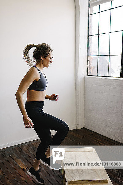 Weibliche Athletin springt auf Holzkiste in Turnhalle