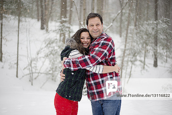 Portrait of happy father embracing daughter while standing on snow covered field in forest