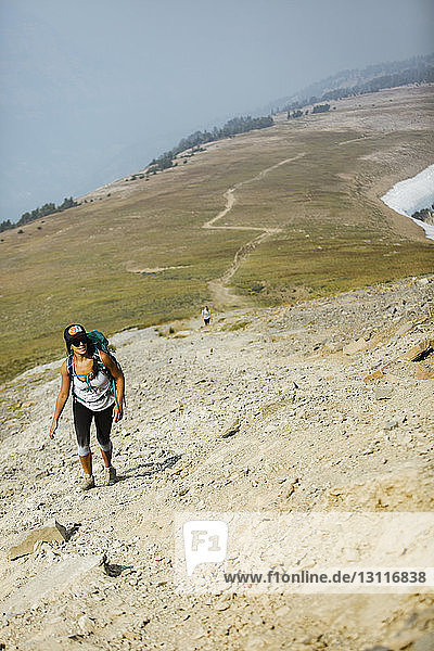 High angle view of hiker with backpack climbing mountain against sky