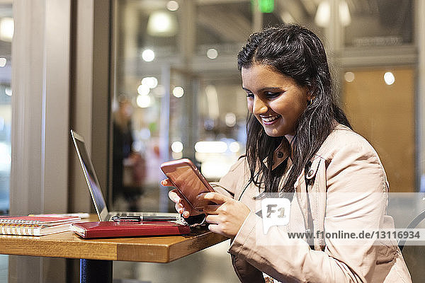 Happy woman using smart phone while sitting at table