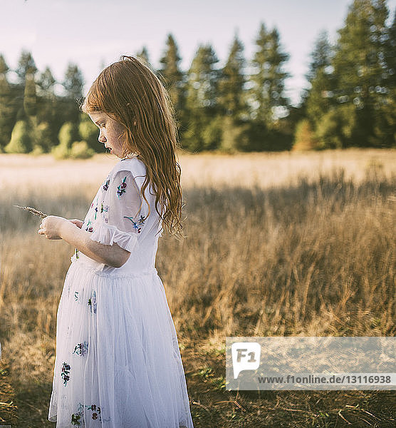 Side view of girl holding plant while standing on field at park