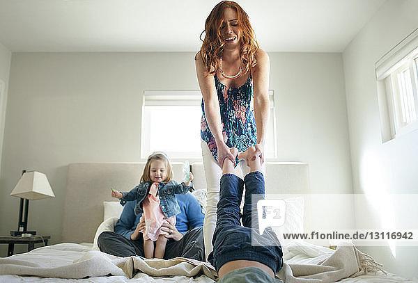 Fröhliche Familie genießt zu Hause im Bett