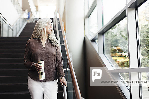 Businesswoman holding bottle looking away while standing on office stairs