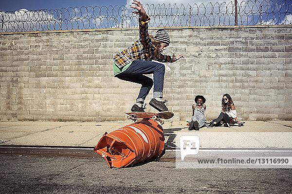 Junger Mann führt Skateboard-Stunt über Fass auf der Straße aus