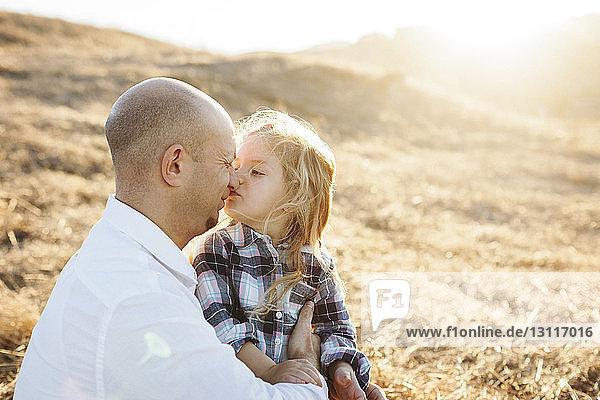 Vater und Tochter reiben sich bei Sonnenschein auf dem Feld die Nasen