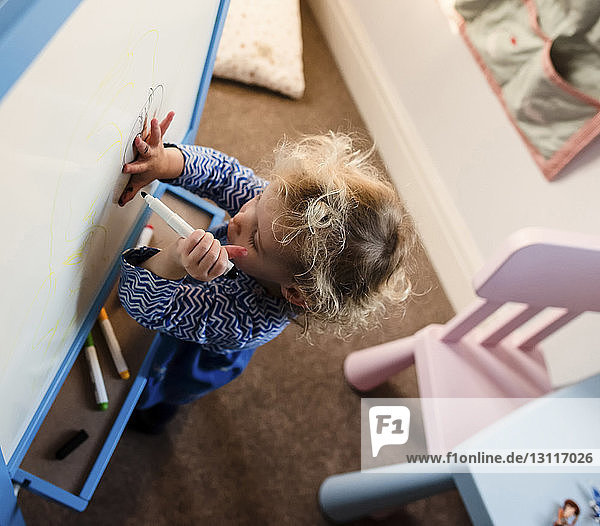 High angle view of girl drawing on canvas at home