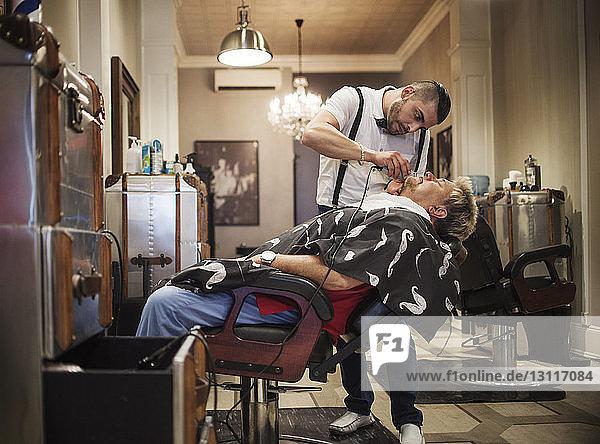 Barber shaving man's beard in shop