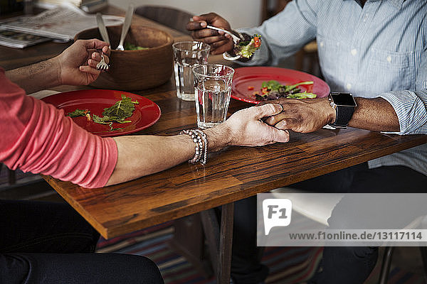 Midsection of gay couple holding hands while eating salad at dining table