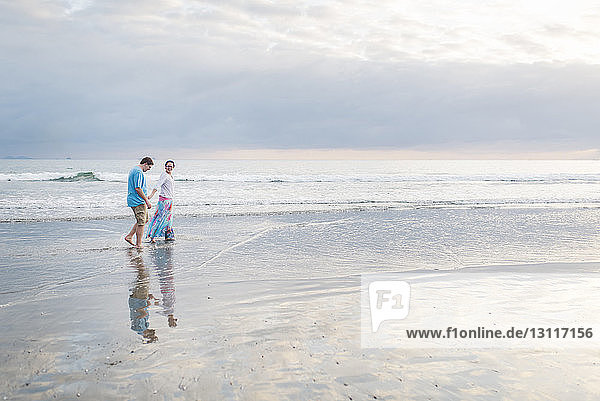 Couple walking on shore at beach against cloudy sky