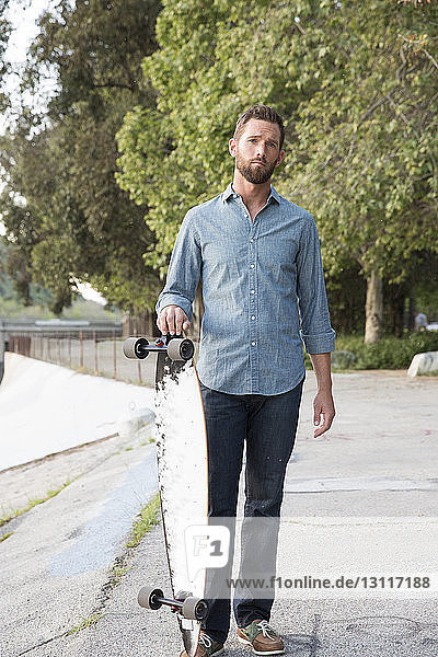 Portrait of handsome man holding skateboard standing against trees