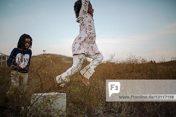 Schwestern spielen bei Sonnenuntergang auf Grasfeld gegen den Himmel