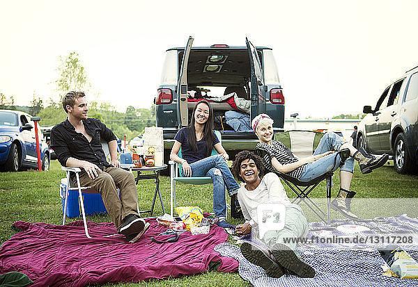 Glückliche Freunde genießen auf dem Campingplatz bei klarem Himmel