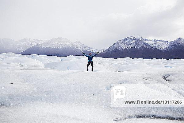 Frau steht auf schneebedecktem Feld vor Bergen