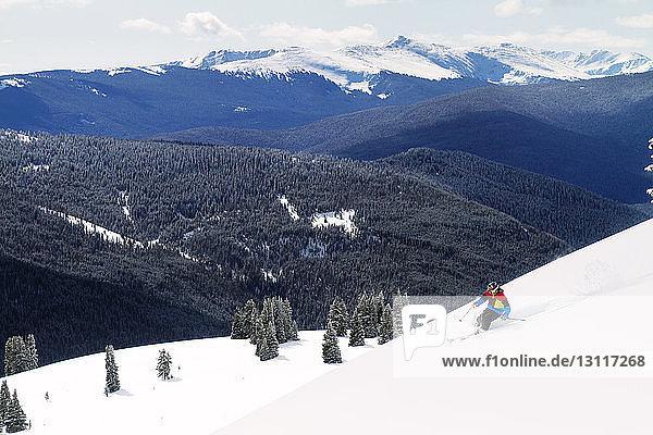 Mann fährt auf Schnee gegen Gebirge