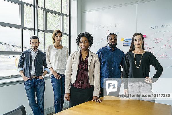 Porträt von selbstbewussten Geschäftsleuten  die im Amt am Tisch stehen