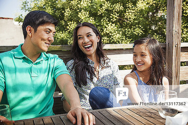 Happy family sitting at table on porch