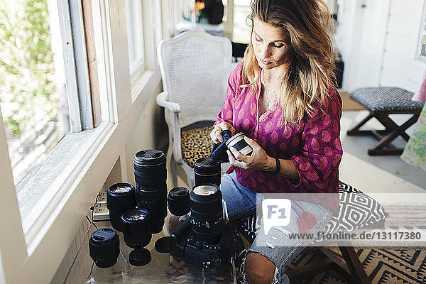 High angle view of woman cleaning camera lens
