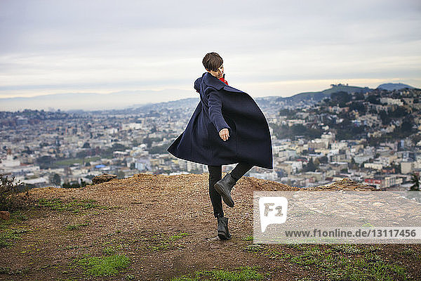 Carefree woman dancing on mountain top with cityscape in background